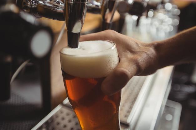 Close-up van barman het vullen bier van barpomp