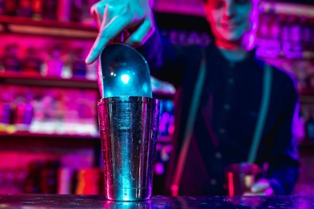 Close-up van barman voltooit de voorbereiding van een alcoholische cocktail in veelkleurig neonlicht