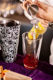Close-up van barmanhanden die alcoholische drank gieten. professionele drank maken