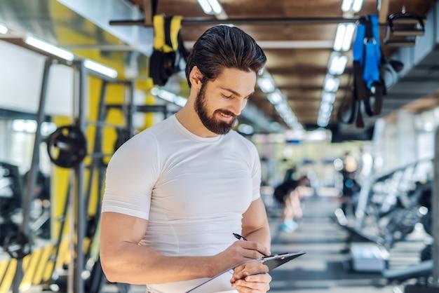 Close-up van bebaarde persoonlijke trainer die op klembordresultaten van opleiding schrijft. gym interieur.