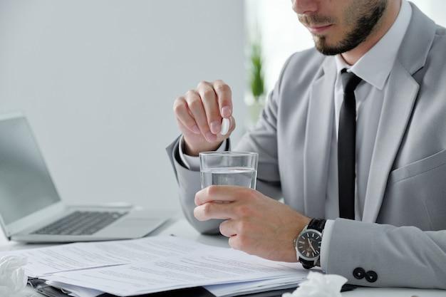 Close-up van bebaarde zakenman zittend aan een bureau met papieren en laptop en het nemen van katerpreventiepil in kantoor