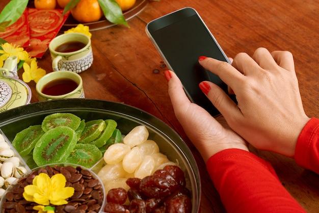 Close-up van bebouwde vrouwelijke handen die smartphone op een gediende dinerlijst houden