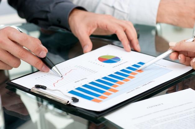 Close-up van bedrijfsmensen die groeiende grafieken analyseren tijdens een vergadering