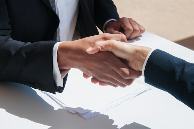 Close-up van bedrijfsmensen die handen in openlucht schudden