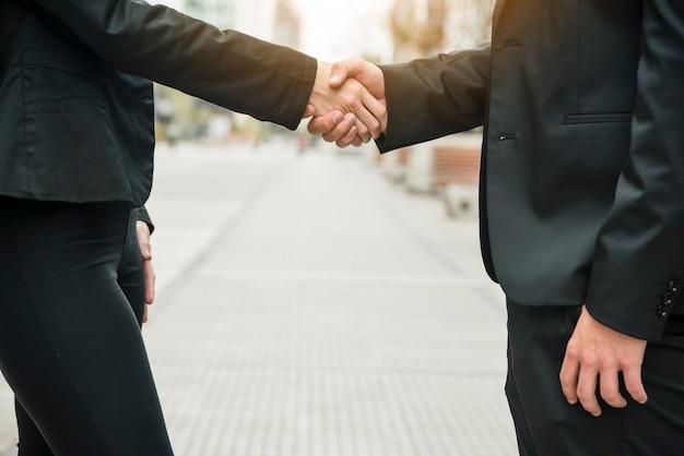 Close-up van bedrijfsmensen die zich op straat bevinden die elkaars hand schudden