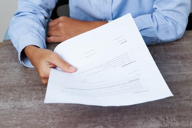 Close-up van bedrijfspersoon die document aan kijker geeft