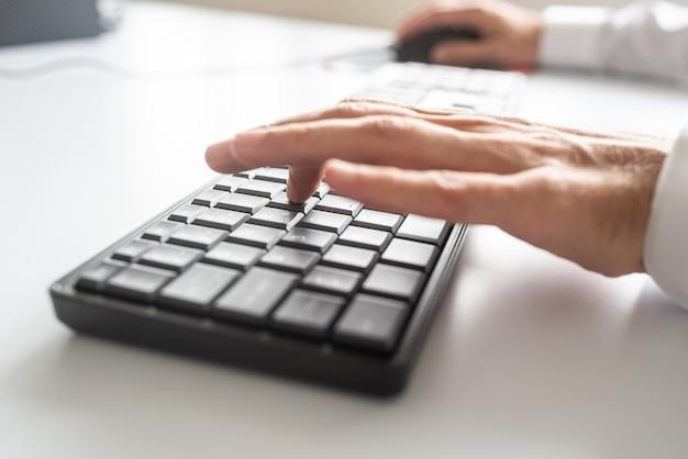 Close-up van bedrijfsprogrammeur die computertoetsenbord en muis gebruikt om aan een project te werken.