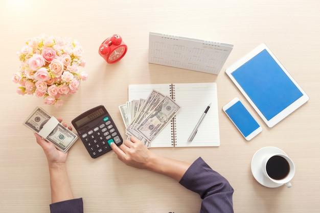 Close-up van bedrijfsvrouw die calculator voor het werken in bureau gebruiken. conceptfinanciering en acco