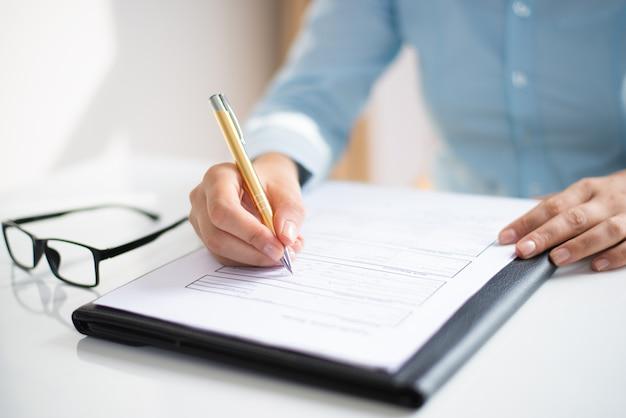Close-up van bedrijfsvrouw die nota's in document maakt