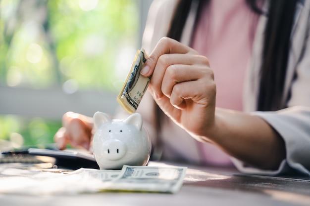 Close-up van bedrijfsvrouwenhand die geld zetten in spaarvarken om geld te besparen. geld besparen en financieel concept