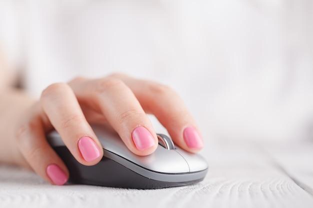 Close-up van bedrijfsvrouwenhand met muis. ondiepe scherptediepte. selectieve aandacht.