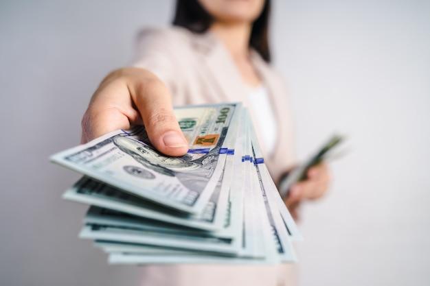 Close-up van bedrijfsvrouwenhanden die geld voorstellen ons dollarrekeningen op wit. geld concept.