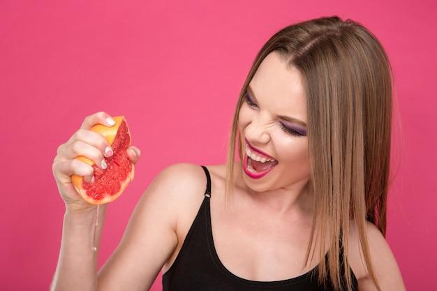 Close-up van behoorlijk opgewonden opgetogen vrouw die grapefruitsap met de handen knijpt
