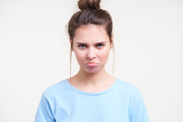 Close-up van beledigde jonge blauwogige brunette dame die haar lippen pruilt terwijl ze droevig naar de camera kijkt, gekleed in een blauw t-shirt terwijl ze op een witte achtergrond staat