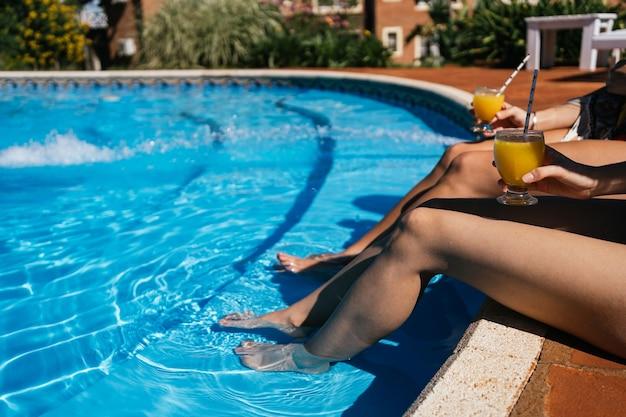 Close-up van benen die van het zwembad genieten