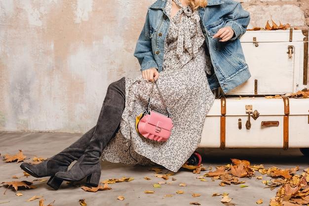 Close-up van benen in hoge suède laarzen van stijlvolle vrouw in spijkerbroek en oversized jas tegen muur in straat