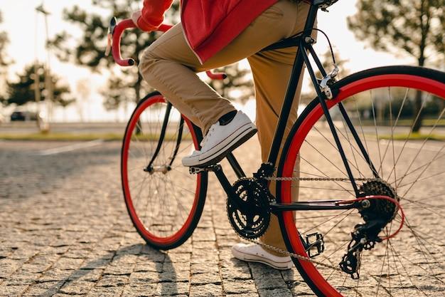 Close-up van benen in sneakers en handen op stuurwiel van hipster stijl bebaarde man in rode hoodie en beige broek alleen rijden met rugzak op fiets gezonde actieve levensstijl reiziger backpacker