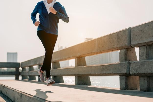 Close-up van benen jonge aziatische vrouwen die 's ochtends joggen in de stad een stad die gezond leeft