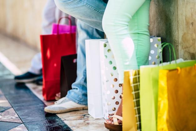 Close-up van benen met boodschappentassen op de grond die een pauze nemen om door te gaan met winkelen - groep mensen op vakantie