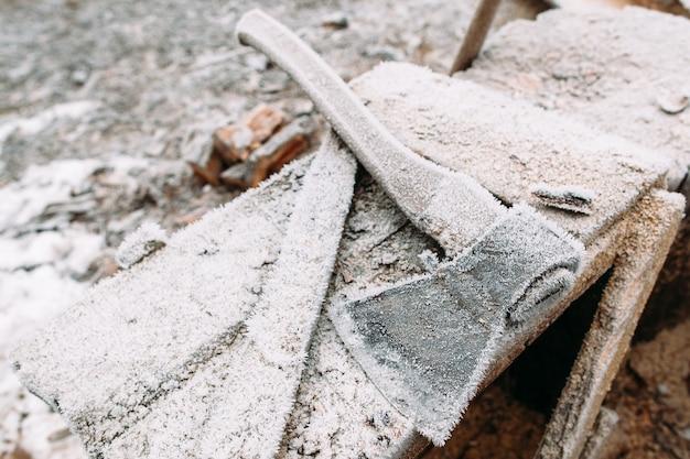 Close-up van berijpte bijl op houten tafel. mechanisch instrument op de werkplek van klusjesman. gereedschap in de winter buiten laten staan. koud, vroege vorst, hoar concept