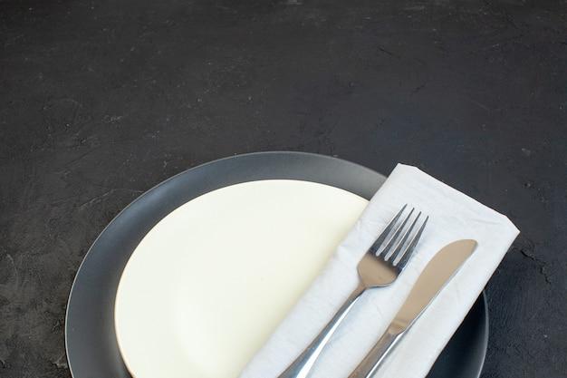 Close-up van bestek ingesteld op wit servet op donkere kleur en witte lege borden in verschillende maten op zwarte achtergrond