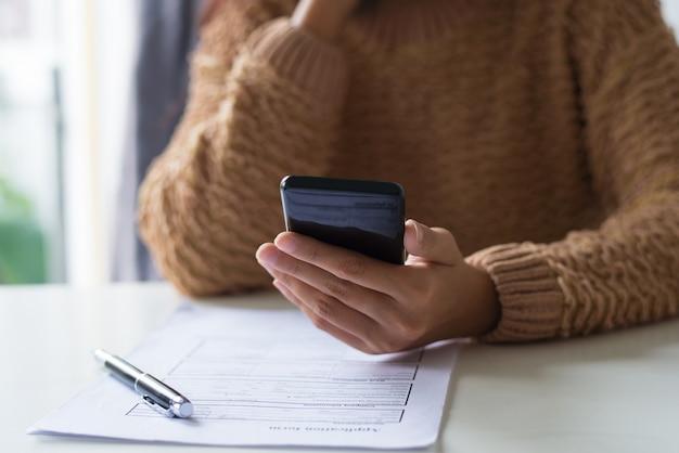 Close-up van bezig dame vullend document en sms op telefoon controleren