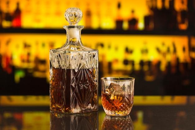 Close-up van bierfles en glas in bar