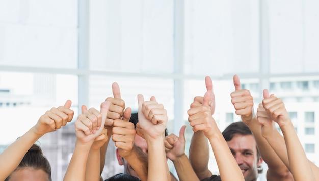 Close-up van bijgesneden mensen gebaren omhoog duimen