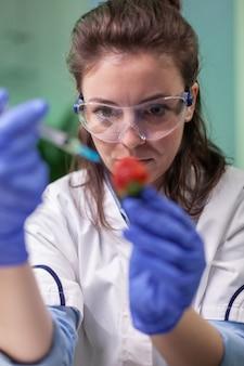 Close-up van biochemicus-onderzoeker die gezonde aardbei injecteert met dna-vloeistof met behulp van een medische spuit die genetische test controleert