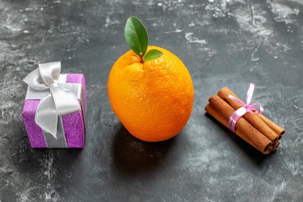 Close-up van biologische verse sinaasappel met stengel en blad in de buurt van een geschenk en kaneellimoenen op donkere achtergrond