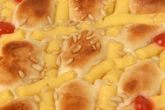 Close up van biscuit van eierroom, pijnboompitten en kersen op witte achtergrond