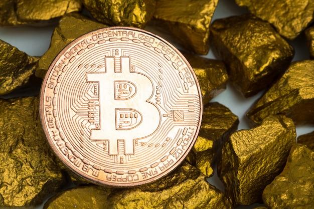 Close-up van bitcoin digitale valuta en goudklompje of gouderts op witte achtergrond, edelsteen of stuk van gouden steen