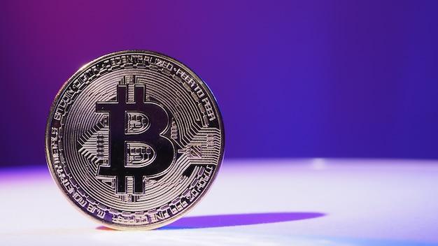 Close-up van bitcoin en digitale beursgrafiekbalk op zwart. cryptogeld. bitcoin-aandelengroei. investeren in virtuele activa. investeringsplatform met grafieken en bitcoin-munt. digitaal geld.
