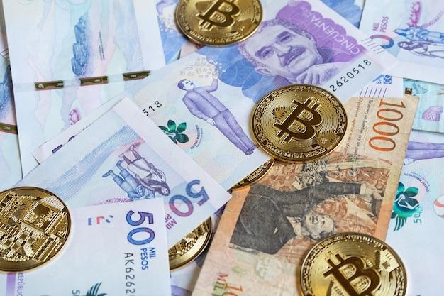 Close-up van bitcoins over colombiaanse bankbiljetten