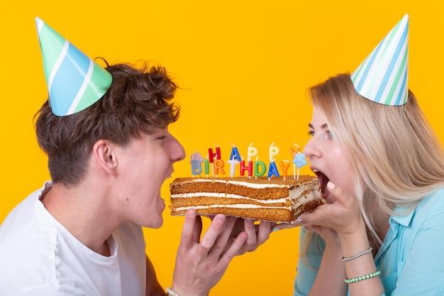 Close-up van bizar jong koppel meisje en jongen in papieren hoeden willen een fluitje van een cent afbijten