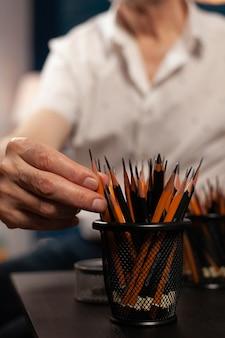Close up van blanke hand op kleurrijke potloden voor beeldende kunst