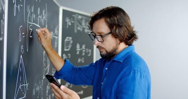 Close up van blanke mannelijke leraar in glazen formules en wiskundige wetten schrijven op bord en smartphone kijken. educatieve wiskundecollege. man docent met behulp van mobiele telefoon als kribbe.
