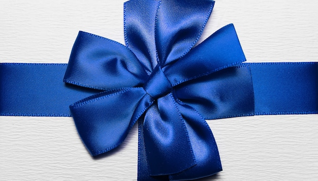 Close-up van blauw inwikkeling lint in vorm van boog voor witte geschenkdoos.