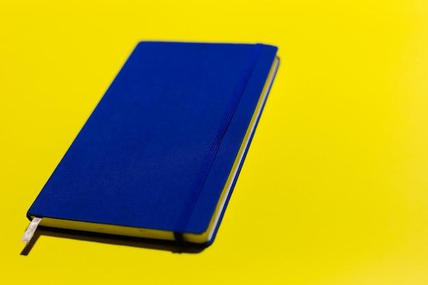Close-up van blauw notitieboekje op gele muur.