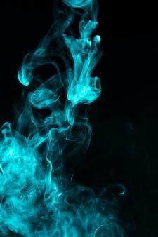 Close-up van blauw rookeffect patroon tegen zwarte achtergrond