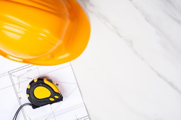 Close-up van blauwdrukken, meetlint en gele bouwhelm. ingenieur concept