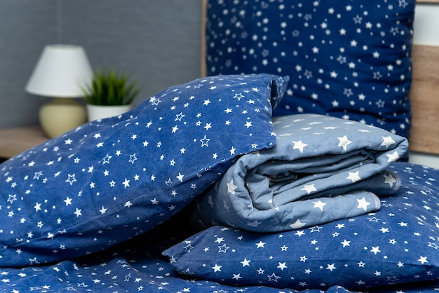 Close-up van blauwe kussens en dekens met een laken op het bed binnenshuis