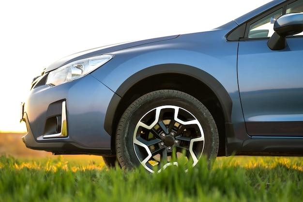 Close-up van blauwe off-road auto op groen gras. reizen met de auto, avontuur in de natuur, expeditie of extreme reizen met een suv-auto. offroad 4x4-voertuig in veld bij zonsopgang.