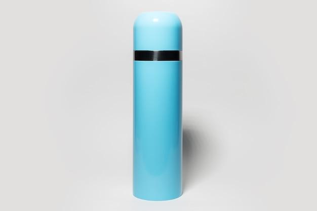 Close-up van blauwe stalen thermos op grijze studio achtergrond.
