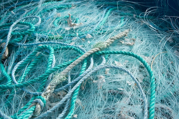 Close-up van blauwe touwen en visnetten op elkaar onder het zonlicht