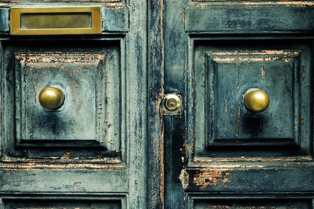 Close-up van blauwe turkoois oude getextureerde antieke deur met gouden brons deurgreep en sleutelgat.