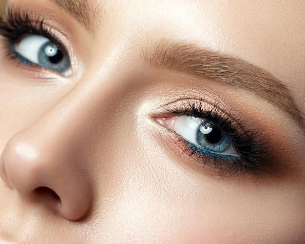 Close-up van blauwe vrouw oog met mooie gouden tinten en zwarte eyeliner make-up. klassieke make-up. perfecte wenkbrauwen.