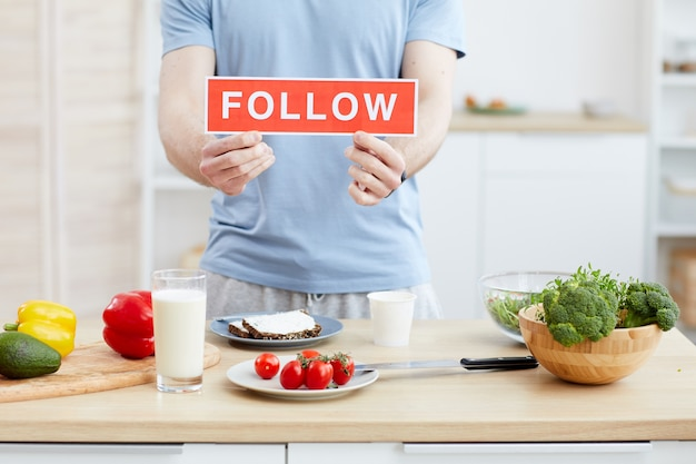 Close-up van blogger met plakkaat volg in zijn handen de blog over gezonde voeding