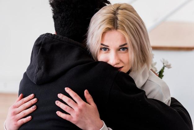 Close-up van blonde jonge vrouw die haar vriend omhelst