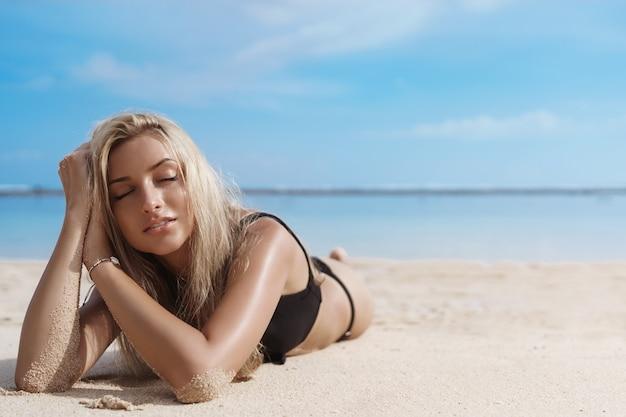 Close up van blonde jonge vrouw gaat liggen op zandstrand.